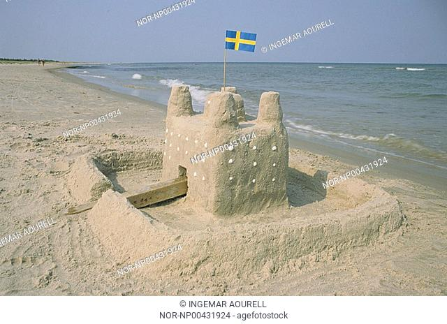 A sand castle on the beach with swedish flag