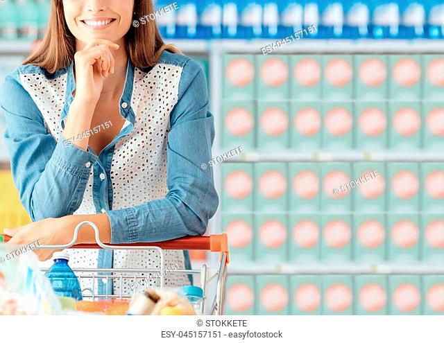 Young smiling woman enjoying shopping at the supermarket, she is leaning on the full cart with hand on chin
