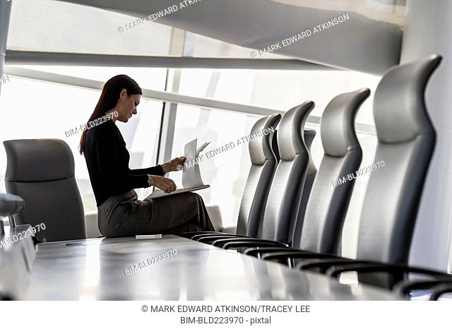 Caucasian businesswoman sitting on conference table reading notepad