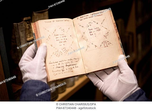 Librarian Heike Mueller shows a book of the mathematician Michael Neander (1529-1581) with sketchings of horoscopes, including that of Martin Luther (R) at the...