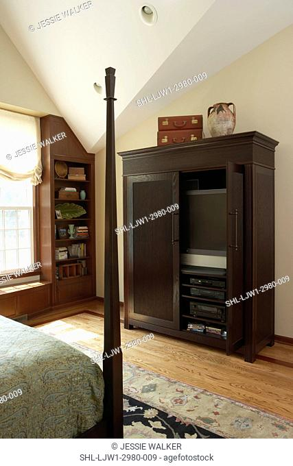 BEDROOM: Contemporary traditional black armoire holds tv open door to reveal tv , built in bookshelves, corner of four poster bed