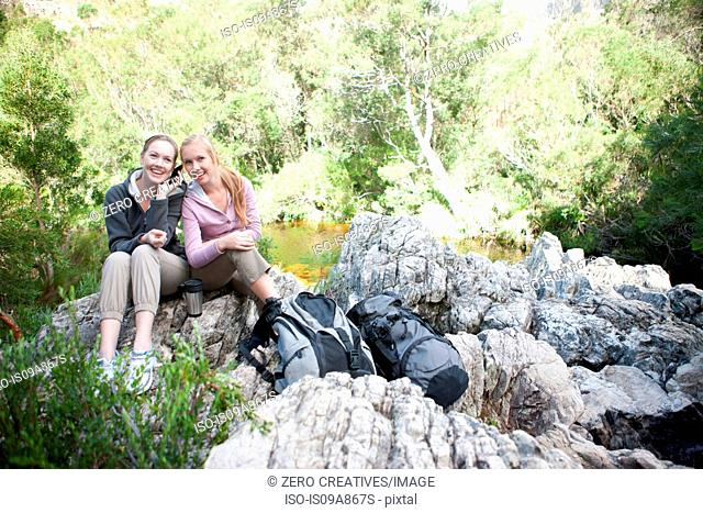 Portrait of girl hikers sitting on rock using cellphone