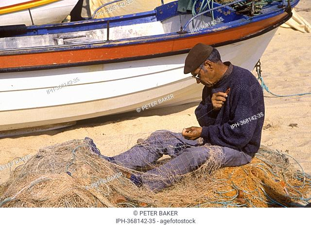 Fisherman mending his nets on the beach at Armacao de Pera on the Algarve