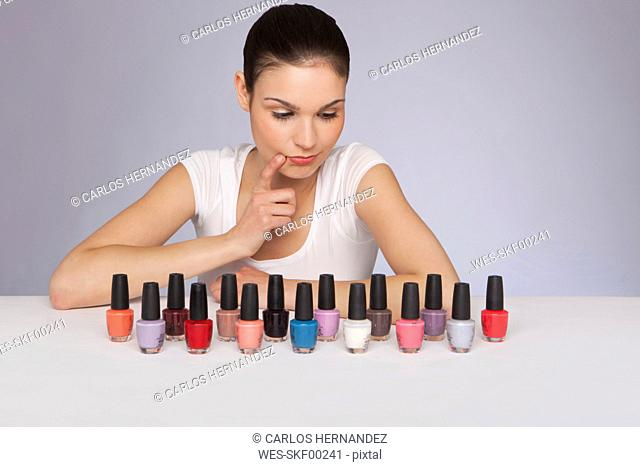 Young woman looking at nail polish bottles