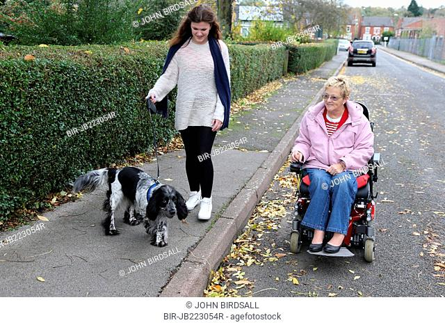 Young girl and wheelchair user talking dog for walk