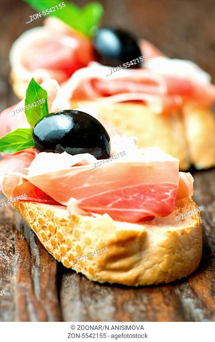 Sandwiches with prosciutto olive on wooden cutting board vertical
