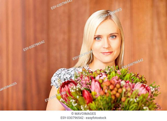 Portrait of a beautiful young woman holding flowers