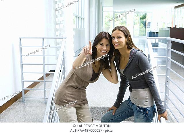 Woman standing on stairs with daughter, pointing, both looking up and smiling