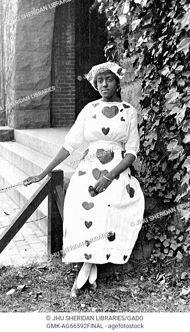 Full length seated portrait of young African American woman, wearing light dress with dark hearts and cap with matching designs