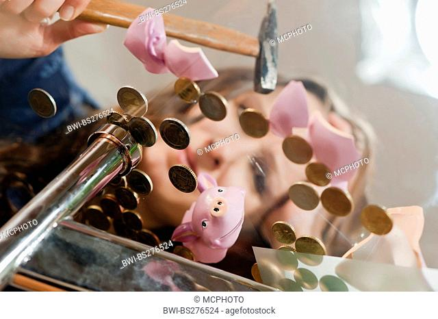 young woman robbing the piggy bank