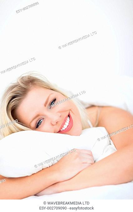 Young woman smiling while embracing a pillow in her bed