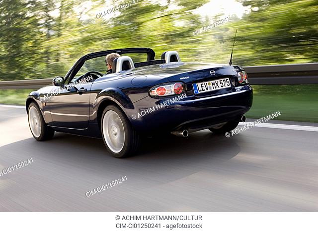 Mazda MX-5 2.0 MZR Roadster Coupe, model year 2006-, blue moving, diagonal from the back, rear view, country road, open top
