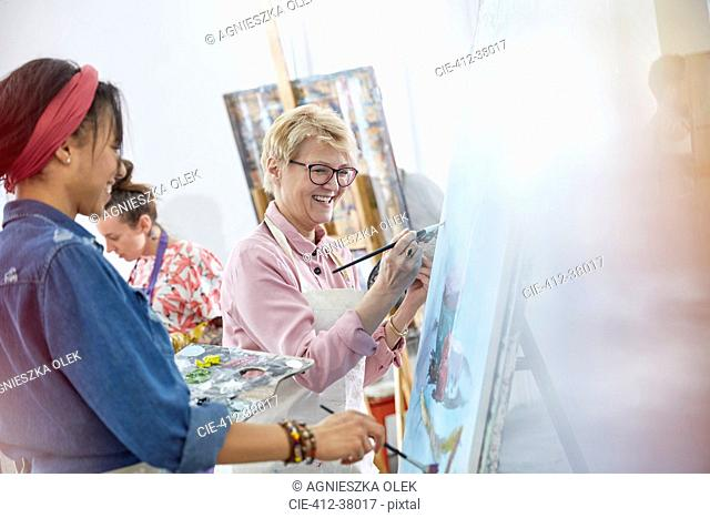 Female artists painting in art class studio