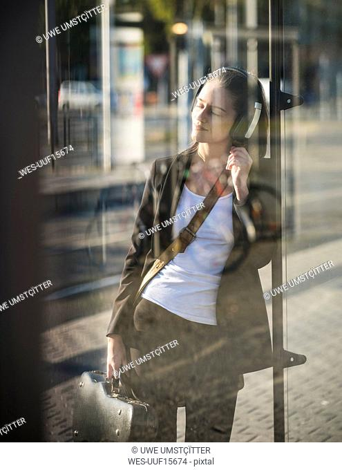 Relaxed young woman listening to music with headphones at tram station