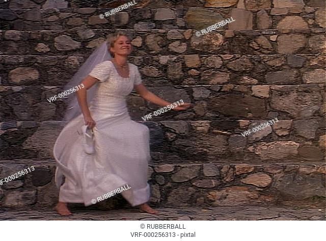 wide shot as a young blonde bride playfully dances in her white wedding dress and veil in front of a stone wall