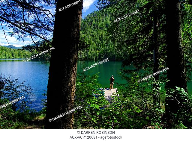 Woman fishes from the dock at Echo Lake Resort near Vernon, British Columbia, Canada - MR1