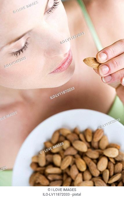 A young woman eating an almond, close-up