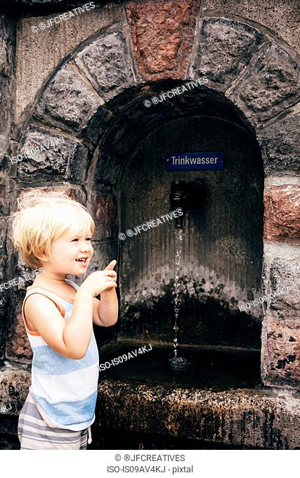 Side view of boy standing by stone drinking fountain, Bludenz, Vorarlberg, Austria