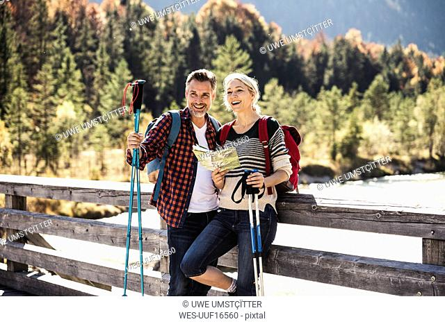 Austria, Alps, happy couple on a hiking trip with map on a bridge
