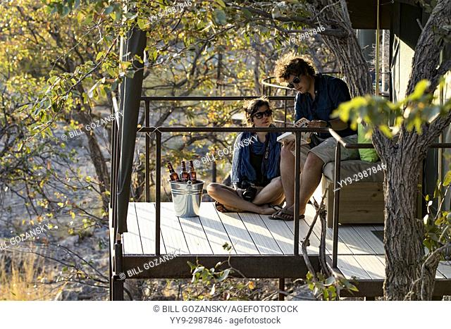 Couple on balcony of tent at Huab Under Canvas, Damaraland, Namibia, Africa