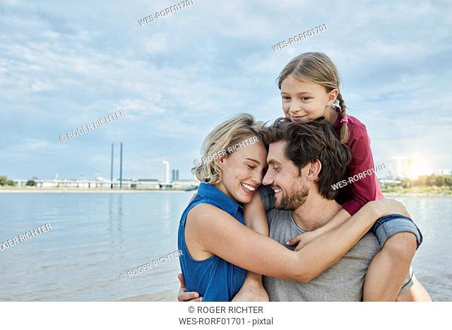 Germany, Duesseldorf, happy family with daughter hugging at Rhine riverbank