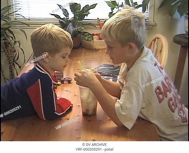 young boys share a milkshake