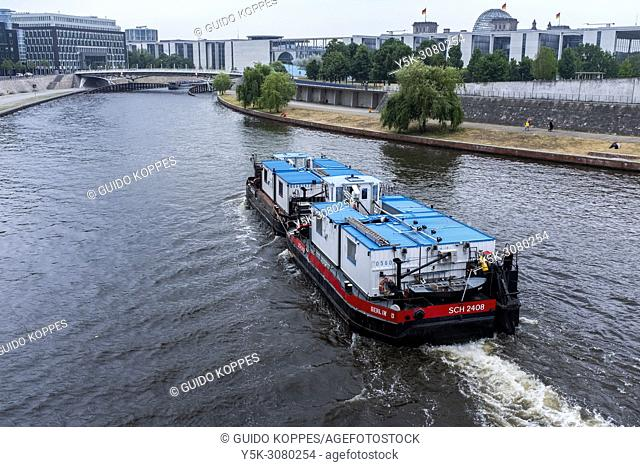 Berlin, Germany. Small Container Vessel, sailing the Spree River, just outside, the political centre of Berlin and approaching Der Reichstag and Der Bundestag