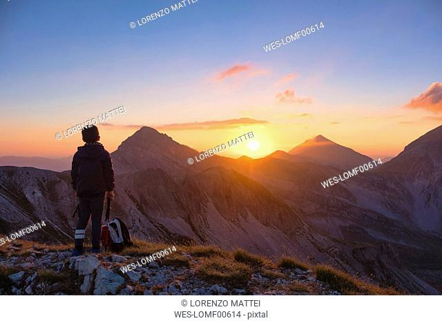 Italy, Abruzzo, Gran Sasso e Monti della Laga National Park, Portella Mountain, hiker watching sunset