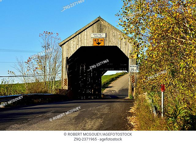 An autumn landscape image showing a one lane wooden covered bridge on a rural road near Sussex New Brunswick Canada under a cloudless blue sky