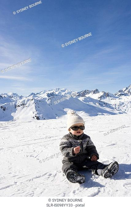Portrait of boy sitting in snow