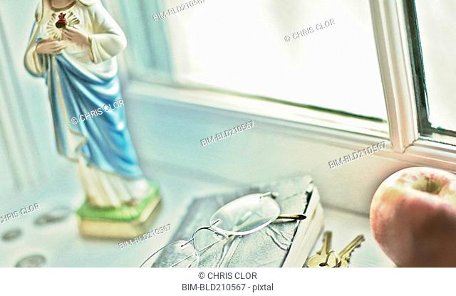 Close up of glasses, religious statue and fruit on windowsill