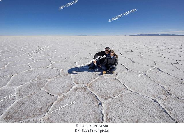 Couple sitting on the salt flats of the Salar de Uyuni; Bolivia