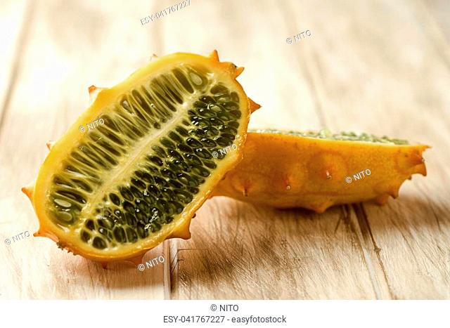 closeup of a kiwano or horned melon cut in halves on a white rustic wooden table