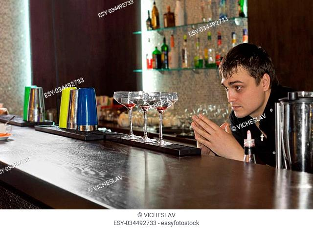 Professional young barman checking three saucer glasses filled with alcoholic cocktail, aligned on the bar