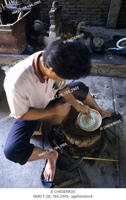 High angle view of a young man making a bowl