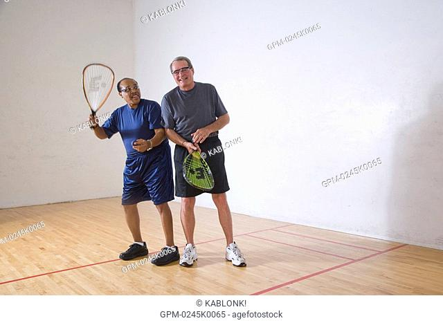 Multi-ethnic senior men playing racketball at indoor court, looking at camera