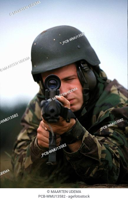 Soldier looking through his telescope and aiming his rifle