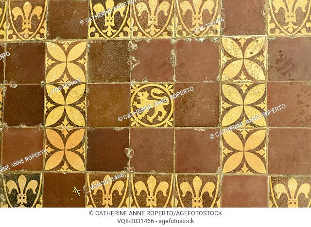 Medieval terracotta tiles showing repeating geometric patterns and fleur de lis and lions passant heraldic motifs in Hereford Cathedral, Hereford, England