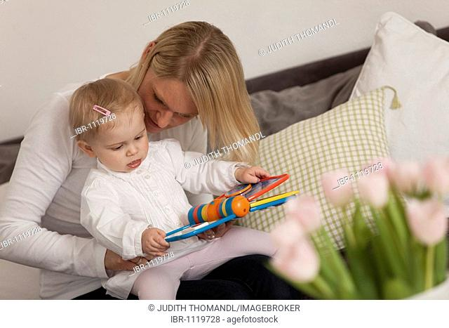 Mother reading a book with her 1-year-old daughter