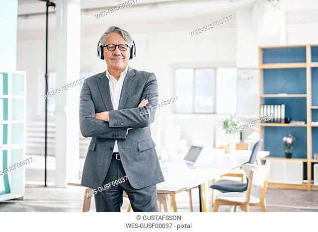 Senior businessman listening to music with headphones in office