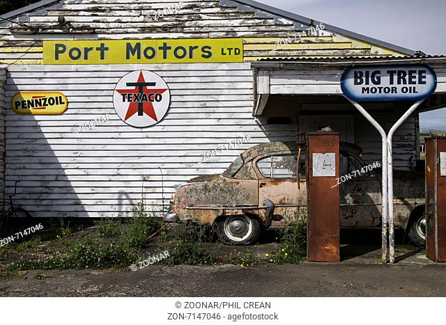 Old abandoned petrol station with a Plymouth Belvedere 1950s car, and two petrol pumps, rotting on the forecourt. Ormondville, New Zealand