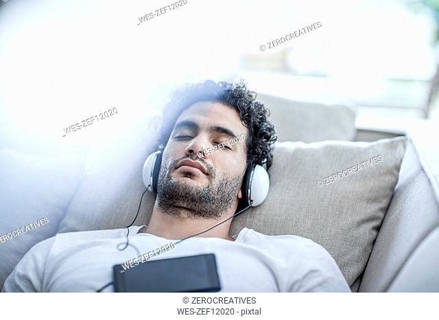 Young man relaxing on couch wearing headphones