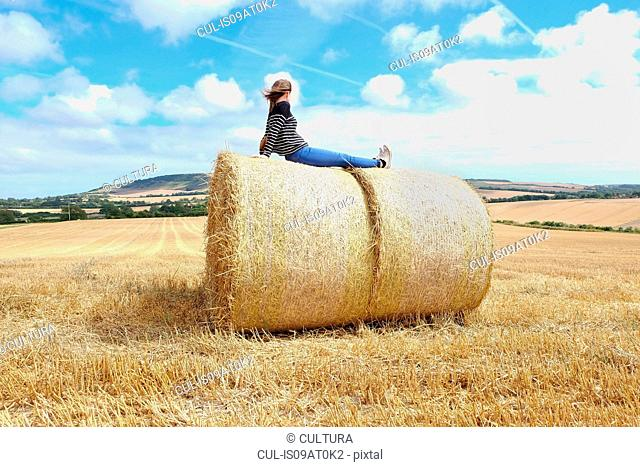 Young woman looking out from top of haystacks in harvested field