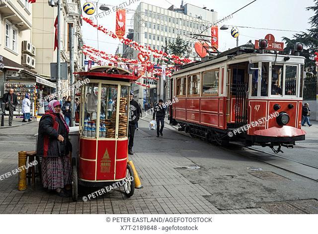 Simit bread vendor and tram in Istiklal Caddesi, Beyoglu, Istanbul, Turkey,