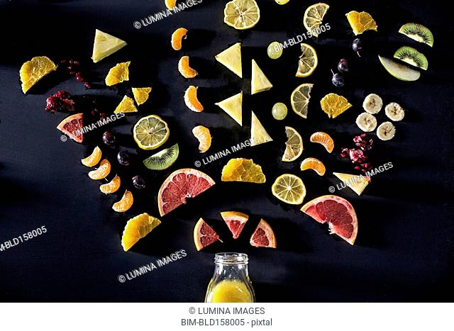 Sliced fruit arranged above juice bottle