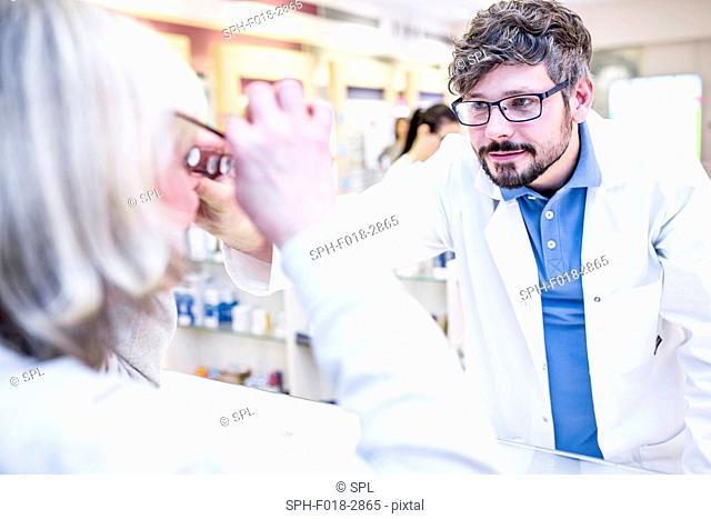 Optometrist trying glasses on woman in optometrist's shop
