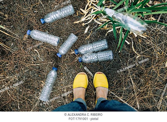 Personal perspective woman standing at littered plastic water bottles
