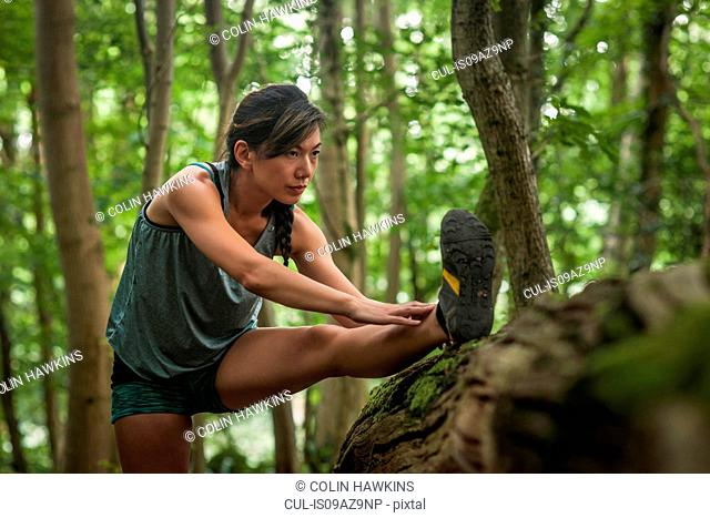 Mid adult woman exercising in forest, stretching