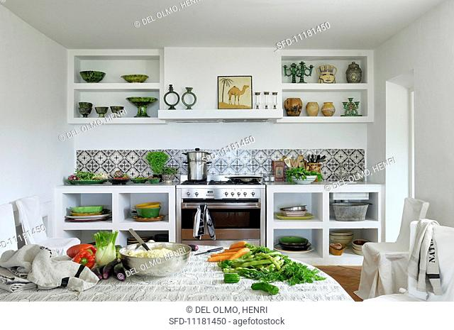 White kitchen units with ceramic tiles; on a large table in the foreground, fresh vegetables and a stainless steel bowl full of couscous