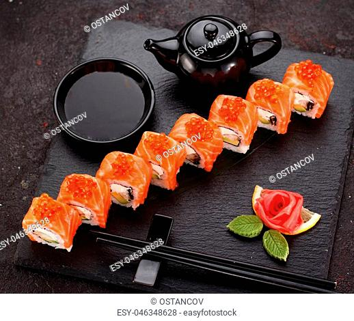 Japanese cuisine. Salmon sushi roll on a stone plate over concrete background